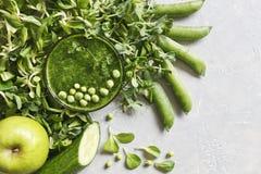 Schließen Sie oben vom selbst gemachten grünen Smoothie mit frischem Spinat, Erbsen, Gurke, Birne und Apfel auf dem grauen Hinter Stockfotos
