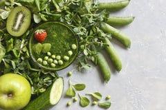 Schließen Sie oben vom selbst gemachten grünen Smoothie mit frischem Spinat, Erbsen, Gurke, Birne und Apfel auf dem grauen Hinter Stockfotografie
