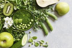 Schließen Sie oben vom selbst gemachten grünen Smoothie mit frischem Spinat, Erbsen, Gurke, Birne und Apfel auf dem grauen Hinter Stockbilder