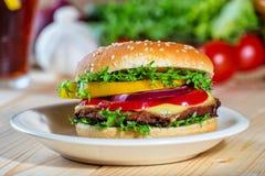 Schließen Sie oben vom selbst gemachten Hamburger auf weißer Platte Lizenzfreie Stockfotos