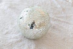 Schließen Sie oben vom silbernen Discoball auf unordentlicher Wolle stockbild