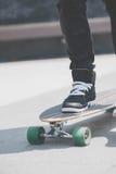 Schließen Sie oben vom skater& x27; s-Beine auf dem longboard Reiten an der Straße herein draußen lizenzfreie stockfotografie