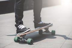 Schließen Sie oben vom skater& x27; s-Beine auf dem longboard Reiten an der Straße herein draußen stockfotos