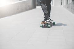 Schließen Sie oben vom skater& x27; s-Beine auf dem longboard Reiten an der Straße herein draußen lizenzfreie stockbilder