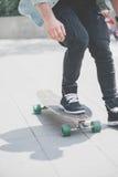 Schließen Sie oben vom skater& x27; s-Beine auf dem longboard Reiten an der Straße herein draußen stockbilder