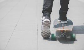 Schließen Sie oben vom skater& x27; s-Beine auf dem longboard Reiten an der Straße herein draußen stockfotografie