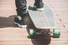 Schließen Sie oben vom skater& x27; s-Beine auf dem longboard Reiten an der Straße herein draußen lizenzfreies stockbild