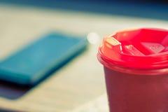Schließen Sie oben vom Smartphone und von der Kaffeetasse auf Tabelle Selektiver Fokus stockfoto