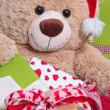 Schließen Sie oben vom smileyteddybären mit Geschenkboxen und Weihnachtshut Stockfotos