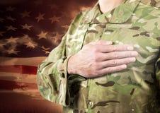 Schließen Sie oben vom Soldaten mit der Hand auf Herzen vor amerikanischer Flagge Stockfotos
