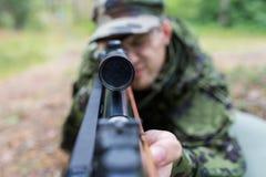 Schließen Sie oben vom Soldaten oder vom Jäger mit Gewehr im Wald Lizenzfreie Stockbilder
