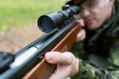 Schließen Sie oben vom Soldaten oder vom Jäger mit Gewehr im Wald Lizenzfreie Stockfotografie