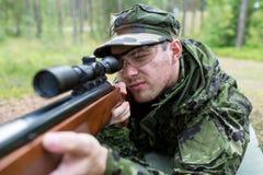 Schließen Sie oben vom Soldaten oder vom Jäger mit Gewehr im Wald Lizenzfreies Stockbild