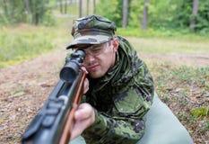 Schließen Sie oben vom Soldaten oder vom Jäger mit Gewehr im Wald Stockfotografie