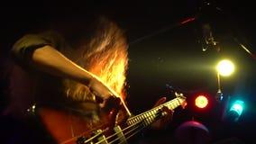 Schließen Sie oben vom Solistmann, der eine Gitarre an einem Rockkonzert spielt Zeitlupe Rockband auf Stufe Hintergrundneonlichte stock footage