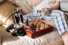Schließen Sie oben vom Spielzeugroboter, der nahes Schachbrett steht Lizenzfreie Stockfotos