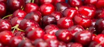 Schließen Sie oben vom Stapel von reifen Kirschen mit Stielen Große Sammlung frische rote Kirschen Reifer Kirschhintergrund Stockbild