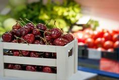 Schließen Sie oben vom Stapel von reifen Kirschen mit Stielen und Blättern Große Sammlung neuer roter Kirschhintergrund Lizenzfreie Stockfotos