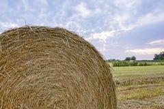 Schließen Sie oben vom Strohballen auf Ackerland mit blauem bewölktem Himmel Stockfoto
