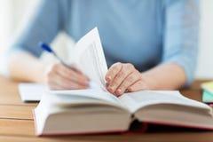 Schließen Sie oben vom Studenten mit Buch und Notizbuch zu Hause Stockfotos