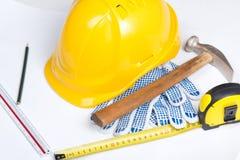 Schließen Sie oben vom Sturzhelm des Erbauers und bearbeiten Sie Werkzeuge über Weiß Lizenzfreies Stockfoto