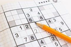Schließen Sie oben vom sudoku Spiel und vom gelben Bleistift Stockfotos