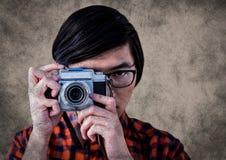 Schließen Sie oben vom tausendjährigen Mann mit Kamera gegen braunen Hintergrund mit Schmutzüberlagerung Stockfoto