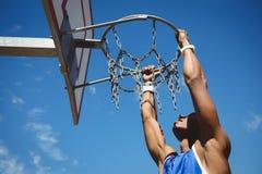 Schließen Sie oben vom Teenager, der am Basketballkorb hängt Lizenzfreie Stockfotografie