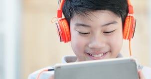 Schließen Sie oben vom Teenager des Asiaten vor, der zu Hause Tablet-Computer mit Lächelngesicht spielt stock video footage