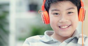 Schließen Sie oben vom Teenager des Asiaten vor, der zu Hause Tablet-Computer mit Lächelngesicht spielt stock footage
