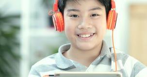 Schließen Sie oben vom Teenager des Asiaten vor, der zu Hause Tablet-Computer mit Lächelngesicht spielt stock video