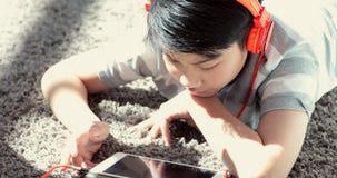 Schließen Sie oben vom Teenager des Asiaten vor stillstehen auf Boden und zu Hause spielen Tablet-Computer mit Lächelngesicht stock footage
