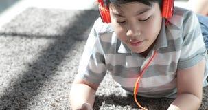 Schließen Sie oben vom Teenager des Asiaten vor stillstehen auf Boden und zu Hause spielen Tablet-Computer mit Lächelngesicht stock video