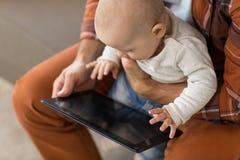 Schließen Sie oben vom Vater- und Babysohn mit Tabletten-PC lizenzfreie stockfotografie