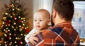Schließen Sie oben vom Vaterholding-Babysohn auf Weihnachten stockfotografie