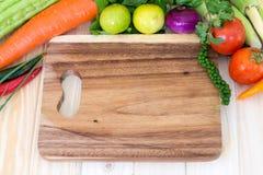 Schließen Sie oben vom verschiedenen Gemüse und Holzklotz für bereiten Koch vor Lizenzfreie Stockbilder