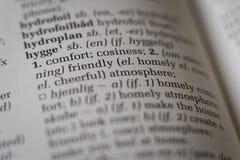Schließen Sie oben vom Wörterbuch mit dem dänischen Wort hygge, das zu Englisch übersetzt wird Stockbild