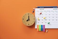 Schließen Sie oben vom Wecker und vom Kalender auf dem orange Tabellenhintergrund lizenzfreie stockbilder
