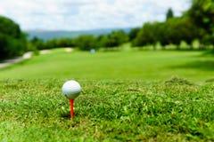 Schließen Sie oben vom weißen Golfball auf orange T-Stück auf grünem Gras mit blauem Himmel und Wolke und von der Ansicht des Geb stockbild