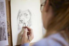 Schließen Sie oben vom weiblichen Jugendkünstler-Sitting At Easel-Zeichnungs-Bild des Hundes von der Fotografie in der Holzkohle lizenzfreies stockfoto