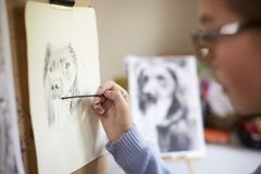 Schließen Sie oben vom weiblichen Jugendkünstler-Sitting At Easel-Zeichnungs-Bild des Hundes von der Fotografie in der Holzkohle lizenzfreie stockbilder