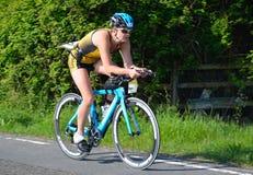 Schließen Sie oben vom weiblichen triathlete auf Radfahrenstadium der Straße stockfotos