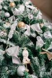 Schließen Sie oben vom Weihnachtsbaum mit Verzierungsflitter, Bogen, Schneeflocken, Kiefernkegeln und Lichtern Stockbilder