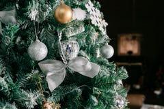 Schließen Sie oben vom Weihnachtsbaum mit Verzierungsflitter, Bogen, Schneeflocken, Kiefernkegeln und Lichtern Lizenzfreies Stockbild