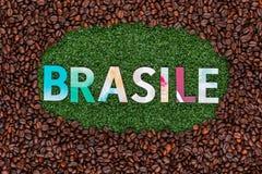 Schlie?en Sie oben vom Wort Brasile auf Gras mit Kaffeebohnen herum stockbild