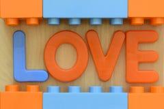 Schließen Sie oben vom Wort LIEBE in den Plastikspielzeugbuchstaben Stockfotos