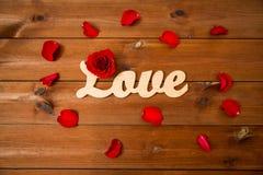 Schließen Sie oben vom Wortliebesausschnitt mit Rotrose auf Holz Lizenzfreie Stockbilder