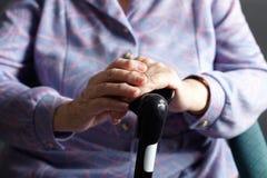 Schließen Sie oben von ältere Frauen-Holding-gehendem Steuerknüppel Stockfotos