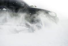 Schließen Sie oben von Autoreifen auf einer schneebedeckten Straße (Fokus auf dem Schnee) Lizenzfreie Stockfotos