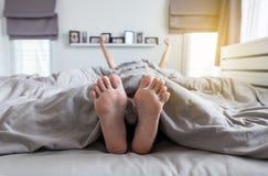 Schliessen Sie Oben Von Barfuss Fusse Und Ausdehnung Faul Auf Dem Bett